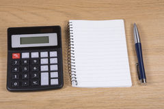 Calculator, notepad and pen on a wooden desk Royalty Free Stock Images