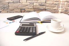 Calculator with notepad and phone on desk royalty free stock image
