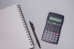 Calculator, notitieboekje en pen op de bureaulijst aangaande witte achtergrond Het concept van de begroting Stock Fotografie