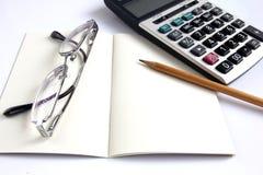 Calculator, notitieboekje, oogglas en potlood Royalty-vrije Stock Fotografie