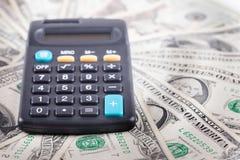 Calculator op de achtergrond van Amerikaanse dollarsbankbiljetten Stock Afbeeldingen
