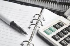 Calculator op Notitieboekje met pen stock afbeelding