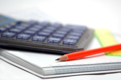 Calculator and orange pencil. Grey translucent calculator and orange pencil Royalty Free Stock Photo