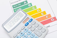 Calculator over colorful energy efficiency chart. Calculator over energy efficiency chart royalty free stock image