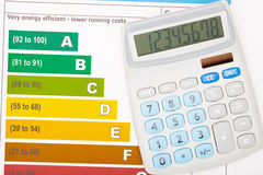 Calculator over colorful energy efficiency chart. Studio shot stock images