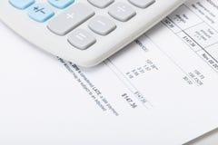 Calculator over utility bill stock photos
