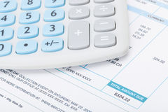 Calculator over utility bill. Studio shot Stock Images