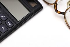 A calculator and a pair of glasses Stock Photos