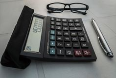 Calculator with a pair of glasses and a pen stock images