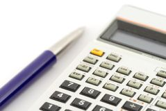 Calculator and a pen. On white background. Shallow depth of field with focus on calculator buttons royalty free stock image