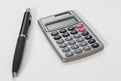 Calculator and a pen. Close-up of a calculator and a pen Royalty Free Stock Photo