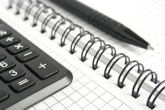 Calculator and pen. Calculator and pen on the background of a notebook Royalty Free Stock Photos