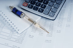 Calculator and pen. On sheets of banking report Royalty Free Stock Image