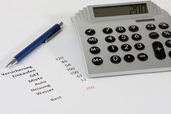 Calculator and a pen along with a negative budget. Closeup of a calculator and a pen along with a negative budget planning Stock Image