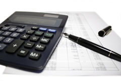 Calculator and pen on balance sheet. Calculator, fountain pen and balance sheet isolated on white background Stock Images