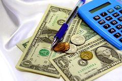 Calculator, pen, banknotes and coins. Royalty Free Stock Photo
