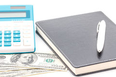 Calculator, pen and black notebook on dollar Royalty Free Stock Photo