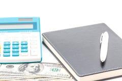 Calculator, pen and black notebook on dollar Stock Photos