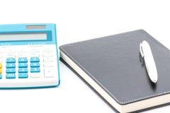 Calculator, pen and black notebook. Stock Photo