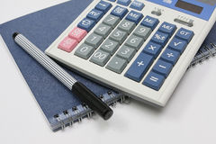 Calculator pen and book. Calculator pen and blue book Royalty Free Stock Photography