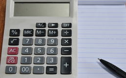 Calculator and pen on book Royalty Free Stock Photography