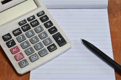 Calculator and pen on book Stock Image