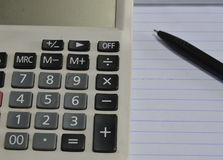 Calculator and pen on book Stock Images