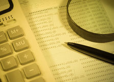 Calculator, pen and business balance. A close-up shot of a calculator  A printed balance sheet and a black ink pen are also visible Stock Image