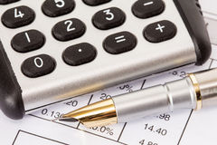 Calculator and pen on  business reports Royalty Free Stock Photos