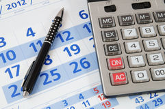 Calculator and pen on calendar Royalty Free Stock Photo