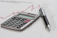Calculator and a pen on a chart. Close-up of a calculator and a pen on a chart Stock Images