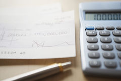 Calculator; Pen And Cheque On Table Royalty Free Stock Images