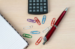 Calculator pen clip and notebook. On a light background royalty free stock photography