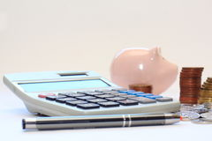 Calculator, pen, coins piggy moneybox. Calculator, pen, coins and piggy bank money box on a light background Royalty Free Stock Photography