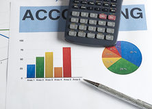 A calculator and a pen on colorful graphics business Stock Image