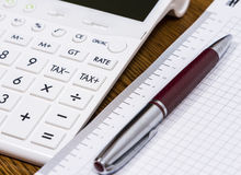 A calculator and a pen on desk. For calculating taxes Stock Images