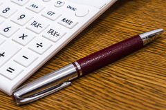 A calculator and a pen on desk Royalty Free Stock Photo