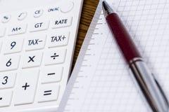 A calculator and a pen on desk Royalty Free Stock Photos