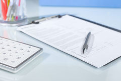 Calculator, pen and documents on a desk Stock Image