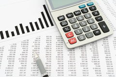 Calculator, pen, documents with numbers and diagram. On white paper stock photos
