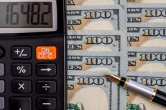 Calculator and pen on dollar. Bills Stock Images
