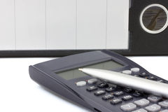 Calculator with pen and dossier on the background Royalty Free Stock Photography