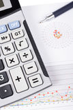 Calculator and pen on earnings chart Royalty Free Stock Images