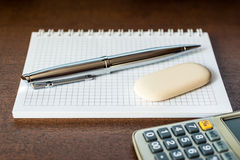 Calculator with a pen and eraser on the table Royalty Free Stock Photo