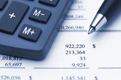 Calculator pen and financial report. Bule macro of calculator, annual finance report and pen that point to big sum in dollars Stock Image