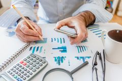Calculator, pen and glasses with financial graphs royalty free stock photography
