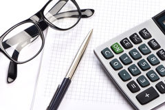 Calculator, pen and glasses isolated Stock Images