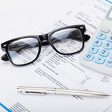 Calculator with pen, glasses and utility bill under it - close up shot Royalty Free Stock Images