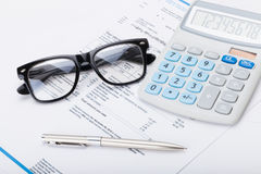 Calculator with pen, glasses and utility bill under it Royalty Free Stock Photo