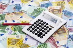 Calculator and pen on heap of euro notes Royalty Free Stock Images